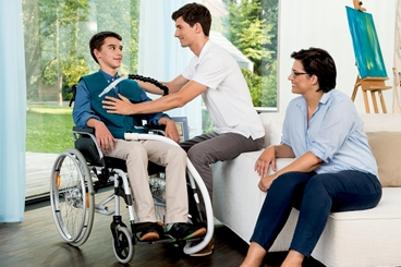 Ventilation patient (boy) with smart vest is sitting in a wheelchair at home. Male nurse is fitting the smart vest. Mother is sitting next to them on the couch.