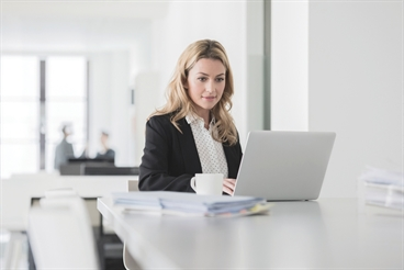 Businesswoman sitting at a desk in an office, working on a laptop.